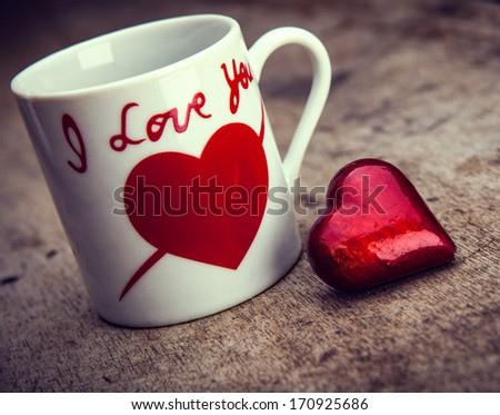 Red heart and mug on wooden background. Valentines day background - stock photo