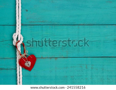 Red heart and silver lock hanging on white rope with knot border against blank antique teal blue rustic wooden background - stock photo