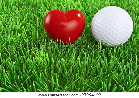 Red heart and white golf ball on the fairway - love golf concept - stock photo