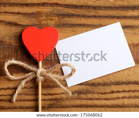 red heart and white paper card on wooden background - stock photo