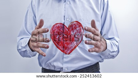 red heart between man's hands on blue gray shirt background close up shoot Idea protection diseases of painted texture sign Healthcare Idea Health or love Valentine day concept  - stock photo