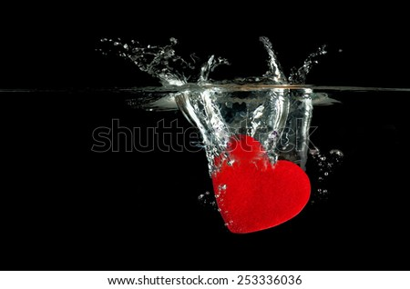 Red heart falling on water splashing. Closeup image isolated on Black background - stock photo