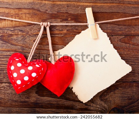 Red heart from fabric handmade Valentines Day hanging on rope on background of vintage wooden texture. Paper tag labeling. - stock photo
