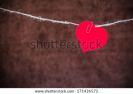 Red heart hanging on a clip on linen rope on dark background - stock photo