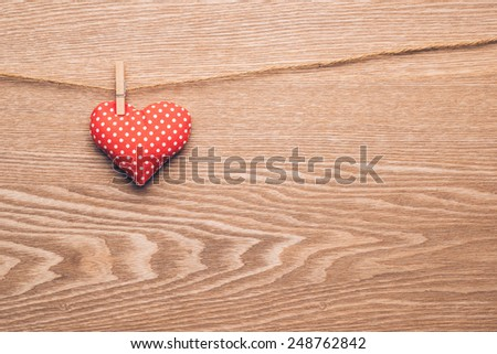 Red heart hanging on the clothesline. On old wood texture background. Valentines day concept - stock photo