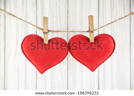 Red heart hangs with a clothespin on a wood a background - stock photo