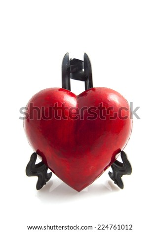 Red heart in black stand isolated over white