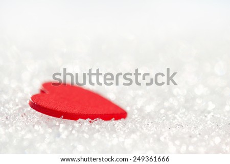 Red heart in glittering snow with red crystals - stock photo