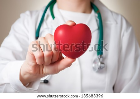 Red heart in the hand of a physician - stock photo