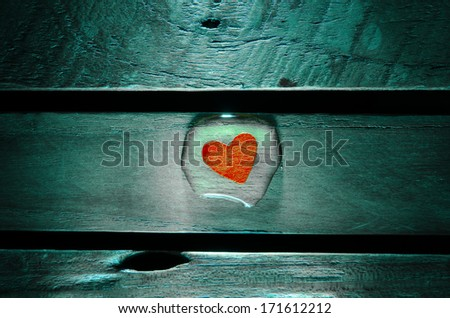 Red heart in water drop on wood pattern background