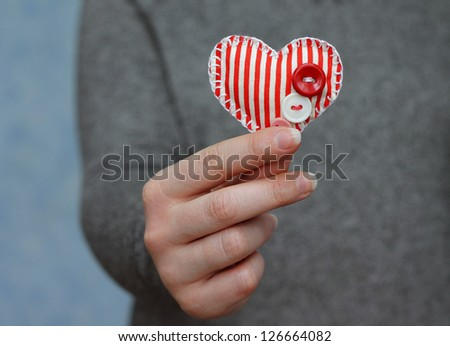 red heart in woman's hand on blue background, close-up - stock photo