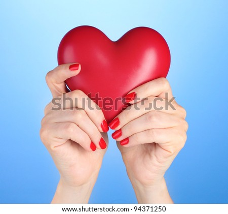 Red heart in woman's hands on blue background