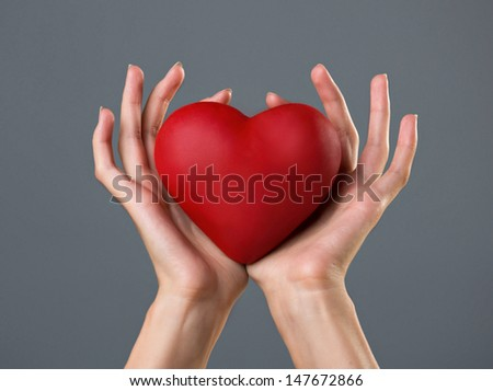 red heart in woman`s palms on grey background