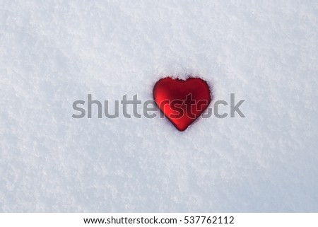 Red heart lies on the snow, the symbol of Valentine's Day, heart melts snow