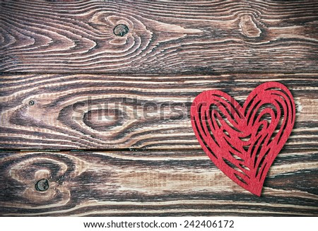 red heart made of felt on the wooden background - stock photo