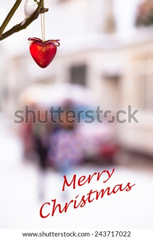 Red heart made of glass hanging on a twig in white winter christmas time at a small town street background with car and children and text merry christmas/Christmas Heart Street Scene - stock photo