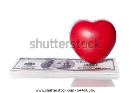 Red heart next to some dollar bills (selective focus) - stock photo