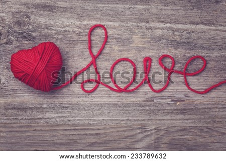 Red heart of red wool yarn on a wooden background - stock photo