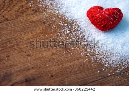 Red heart of red wool yarn on white snow winter and wooden background. Love and St. Valentines Day concept. Close up - stock photo