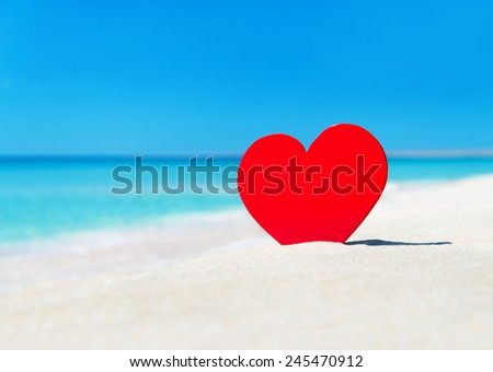 Red heart on ocean beach sand - love concept for holidays - stock photo
