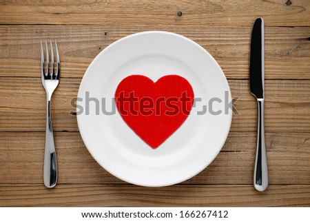 Red heart on plate on wooden background - stock photo