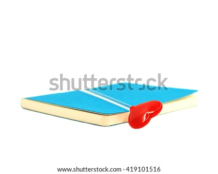 Red heart on the open blue book isolated on white background, select focus.  - stock photo