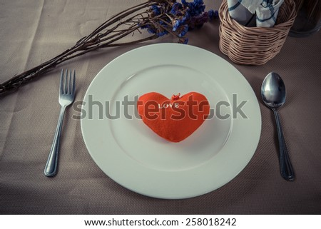 Red heart on white plate.