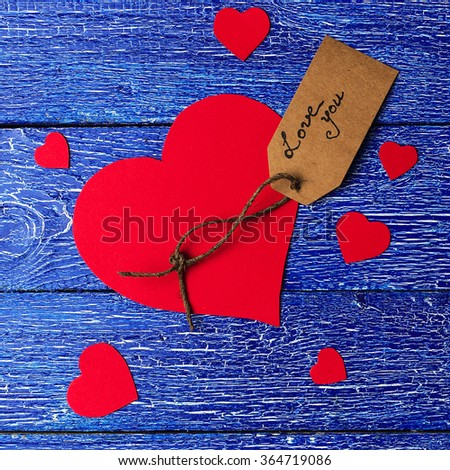 Red heart paper cut with craft label on blue wooden background. Square composition for Valentines day. - stock photo