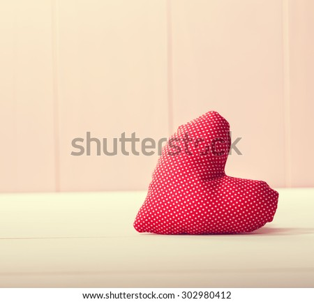 Red heart pillow on pink wooden wall - stock photo