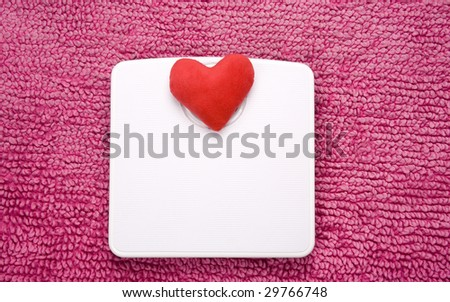 Red heart placed on weight area of scales, shot landscape. - stock photo