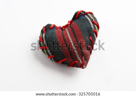Red heart, plaid fabric on isolated background  - stock photo