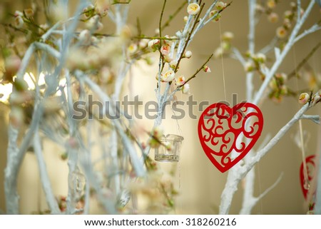 Red heart shape on blooming branches , love symbol for valentine's day or mothers day. - stock photo