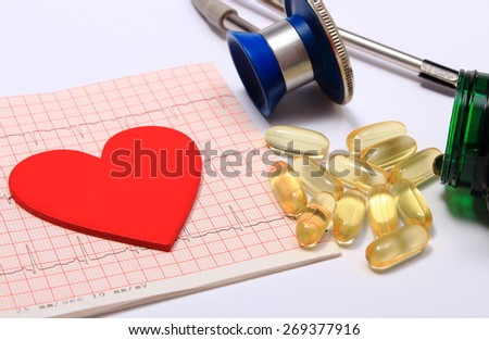 Red heart shape on electrocardiogram graph and medical stethoscope with tablets, ekg heart rhythm, medicine concept - stock photo