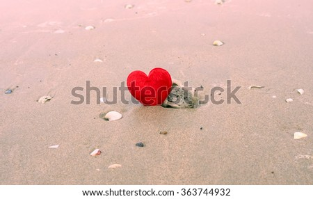 Red heart shape on sand beach under sunset and warm light colored filter. - stock photo