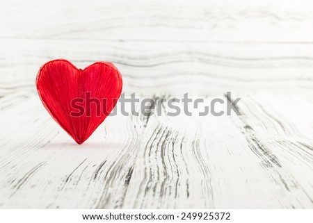 Red heart shape on white vintage wooden background. Valentines Day background. Shallow depth of field - stock photo