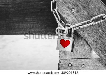 Red heart shape over rustic padlock on wooden bridge over black and white background - stock photo