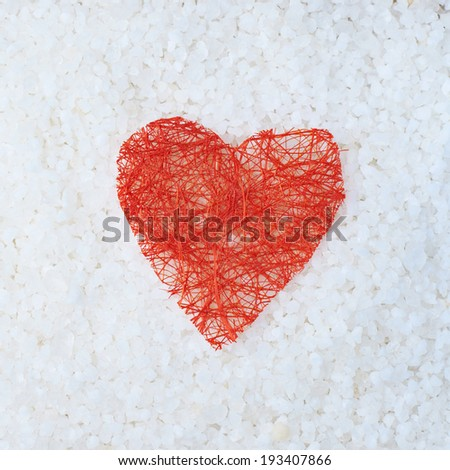 Red heart shape over the surface covered with aromatic salt as a background composition - stock photo