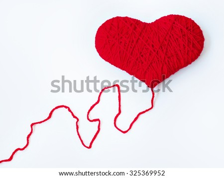 Red heart shape symbol made from wool isolated on music notes - stock photo