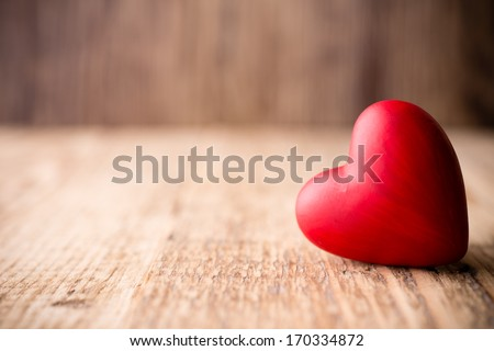 Red heart-shaped candy on a wooden background. - stock photo
