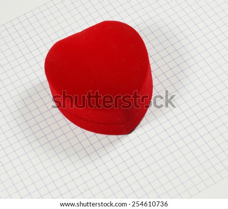 Red heart shaped jewelery box on notebook grid - stock photo