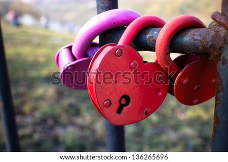 Red heart-shaped locks on fence - stock photo