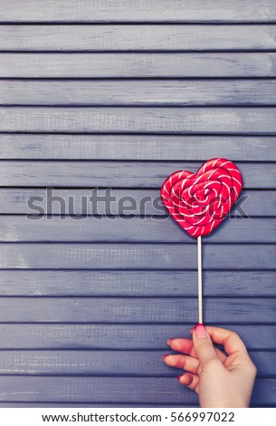 Red heart shaped lollipop candy on stick shot on wooden background.Saint Valentines Day and love concept.Celebrate 14 February with taste heart shape candies.Empty space to place text.Girl hold sweets