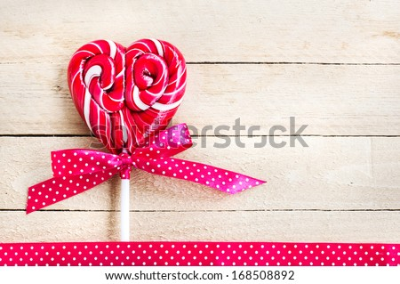 Red heart-shaped lollipop of valentines day on wooden background/ Valentines day background - stock photo