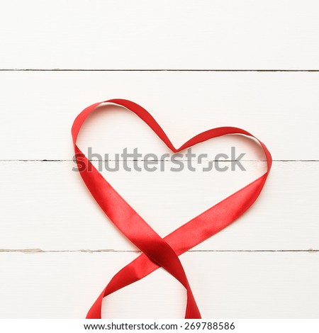 Red heart shaped ribbon over white wooden background - stock photo