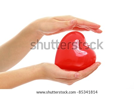 Red heart symbol in woman's hands isolated on white - stock photo