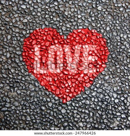 Red heart symbol on the grainy asphalt texture - stock photo
