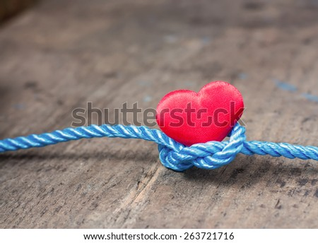 Red heart with a bundle on a wooden board