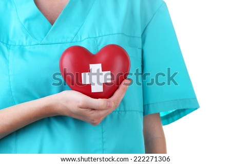 Red heart with cross sign in doctor hand, close-up, isolated on white - stock photo