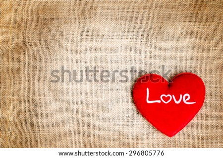 Red heart with love text on gunny sackcloth texture background with grunge retro tone - stock photo