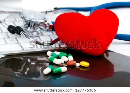 red heart, with pills, tablets, capsule, stethoscope and keyboard on black roentgen, x-ray - stock photo